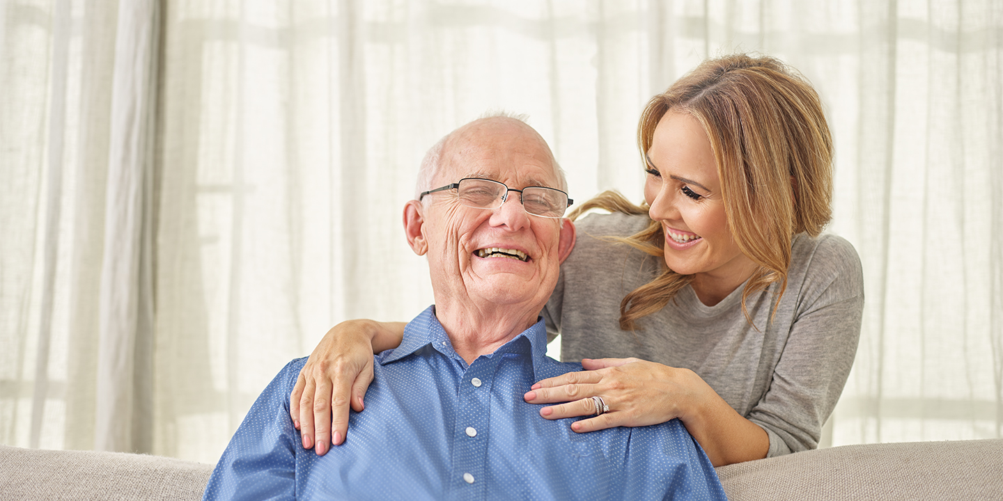 Smiling elderly man with smiling adult daughter, Life Care Gaynes Park Suites