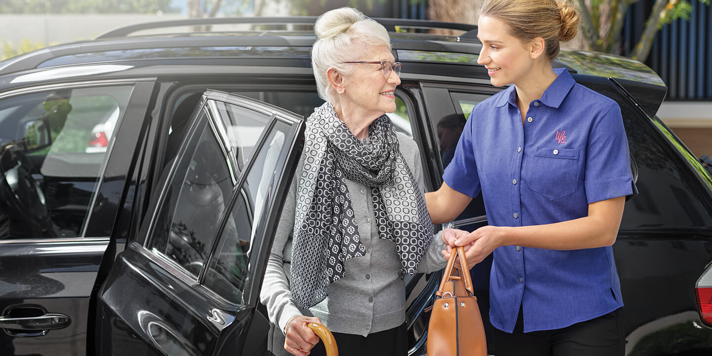 Staff member assisting elderly woman from car, Life Care Gaynes Park Suites